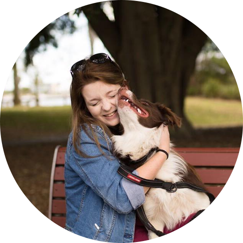 a smiling brunette woman with a border collie