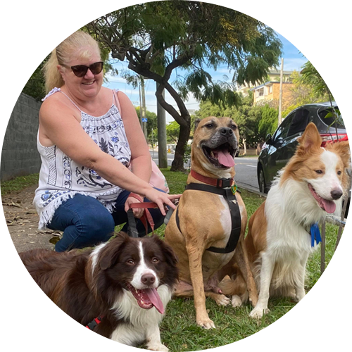 a smiling blonde woman with three dogs