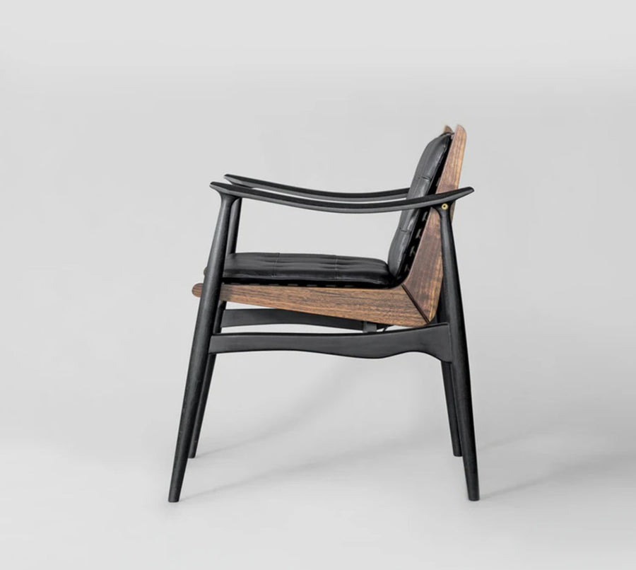Side view of brown and black wood design chair with leather cushion by furniture design studio, Atra. Represented by art gallery Tuleste Factory in New York City.