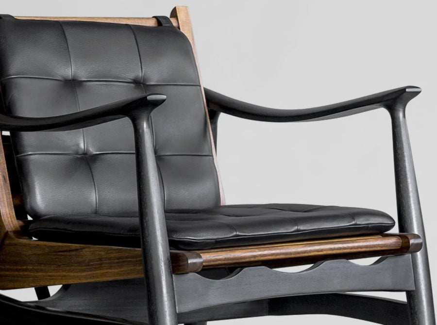 Close up detail shot of Brown and black wood design chair with leather cushion by furniture design studio, Atra. Represented by art gallery Tuleste Factory in New York City.