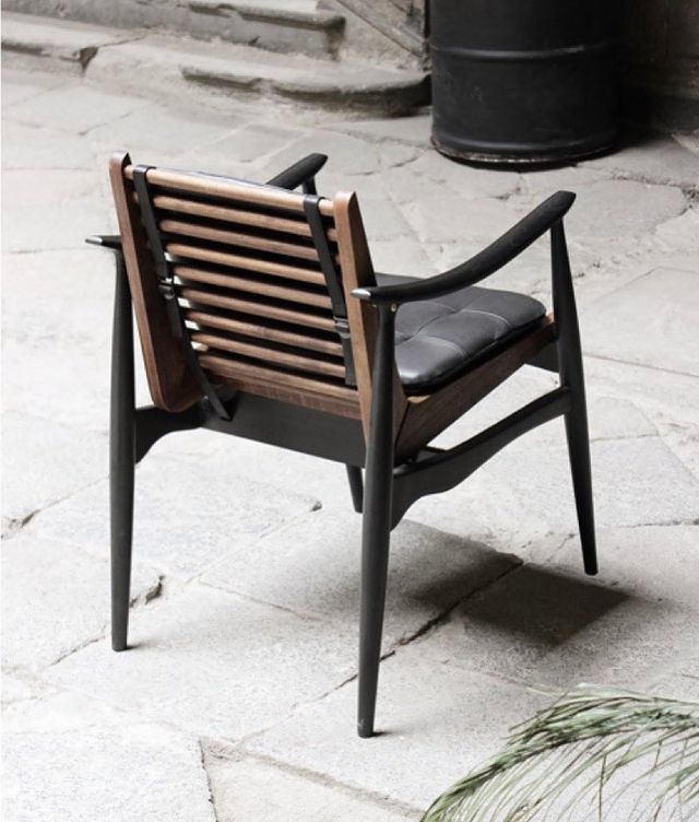 Back view of brown and black wood design chair with leather cushion by furniture design studio, Atra. Represented by art gallery Tuleste Factory in New York City.