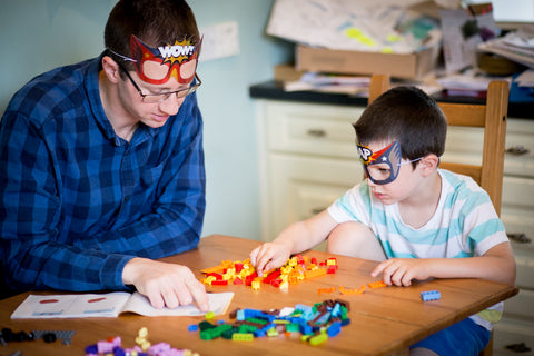 Father and son playing Lego with superhero masks on