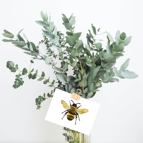 Picture of a watercolour bee greeting card attached to a bouquet of eucalyptus