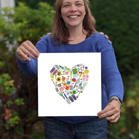 Photo of Anna Hamill, owner of and Hope designs in her garden in Belfast holding one of her gardening heart prints
