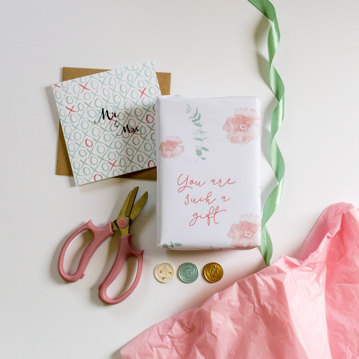 Image of a present wrapped in elegant and Hope designs gift wrap, a mr & Mrs wedding card and elements in mint green and light pink