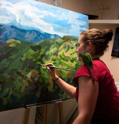 Photo of Joanne Hastie painting a large landscape painting
