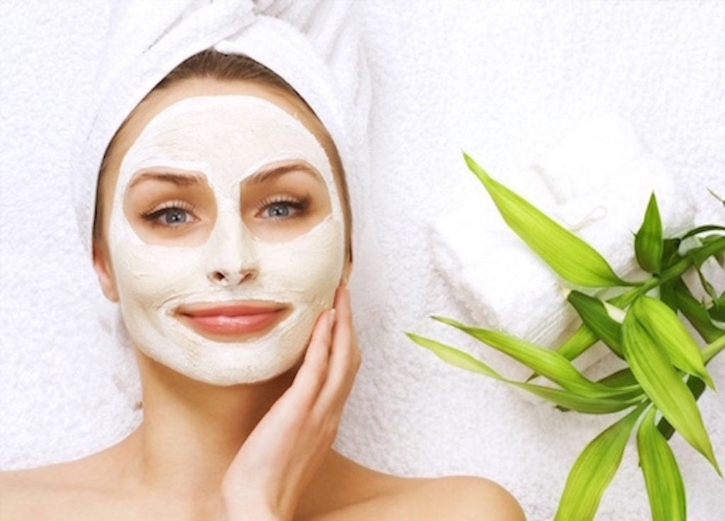 woman smiling with a towel on her head and a spa style facemask.