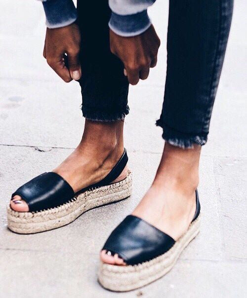a woman wear espadrilles and pulling down her pant leg.