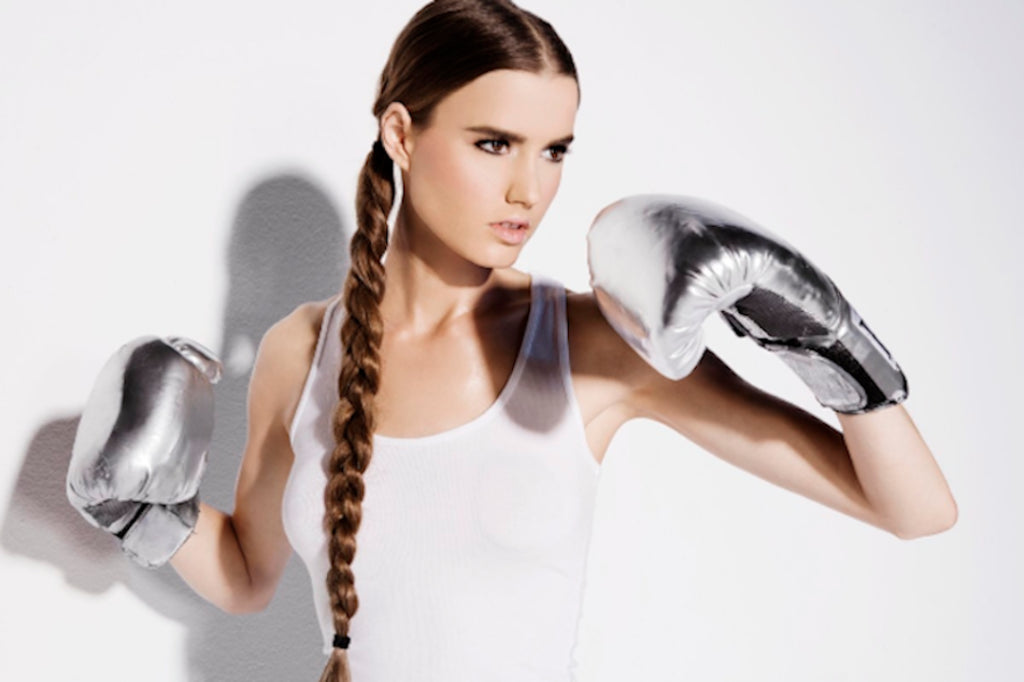 a girl in metallic boxing gloves with a long braid.