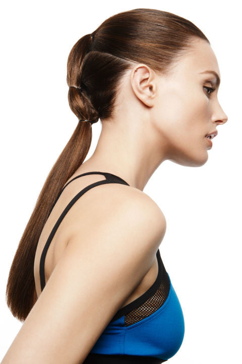 a woman in her sports bra with a could multiple ponytail hairstyle.