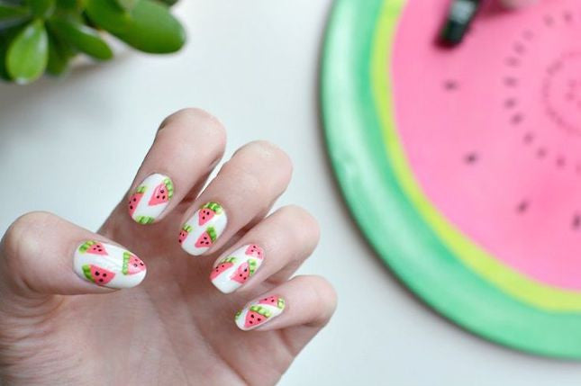 Nails decorated with slices of watermelon.