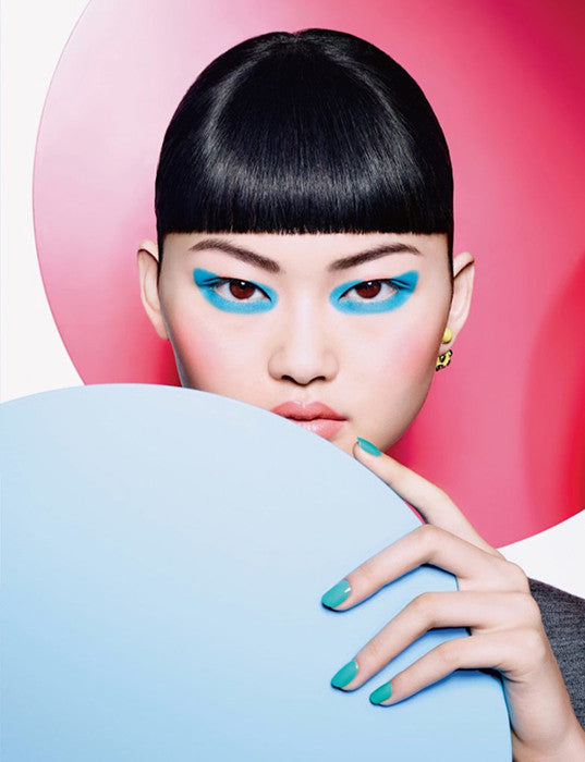 Model wearing bright blue eyeshadow and nail polish.
