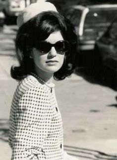 Jackie Kennedy wearing a patterned jacket, large glasses, and a hat