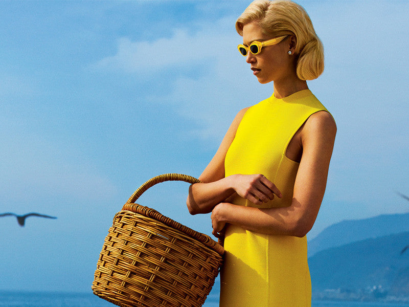 woman holding a wicker picnic basket on the beach