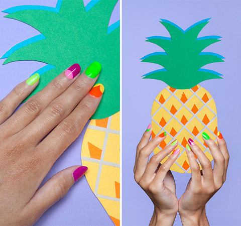 Summer nail polish colors on girl holding cut-out pineapple