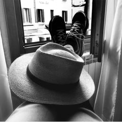 Feet up with straw fedora on knees
