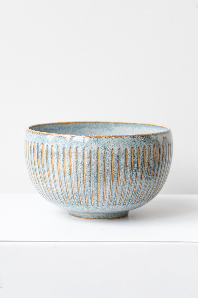 Indigo Fog Horsetails Bowl by Kotobuki sits on a white surface in a white room