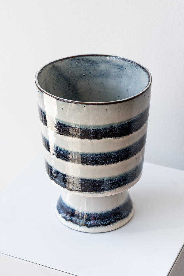 Striped blue and white glazed Toku chalice vase by Homart on a white surface in a white room