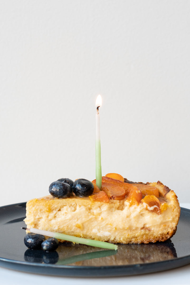 Knot and Bow beeswax candle stuck in slice of cheesecake on blue plate with blueberries and apricots in front of white background