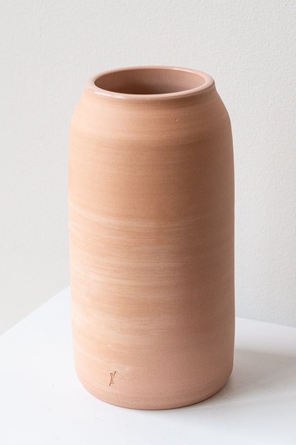 One medium pink ceramic bouquet vase sits on a white surface in a white room. The vase is empty. It is photographed closer and at an angle.