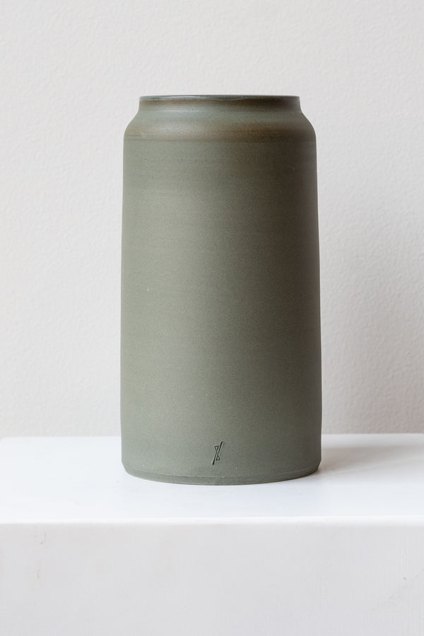 One medium green-grey stoneware vase sits on a white surface in a white room. It is round and tall, and it has a small logo imprinted at the base of the vase. It is photographed straight on.