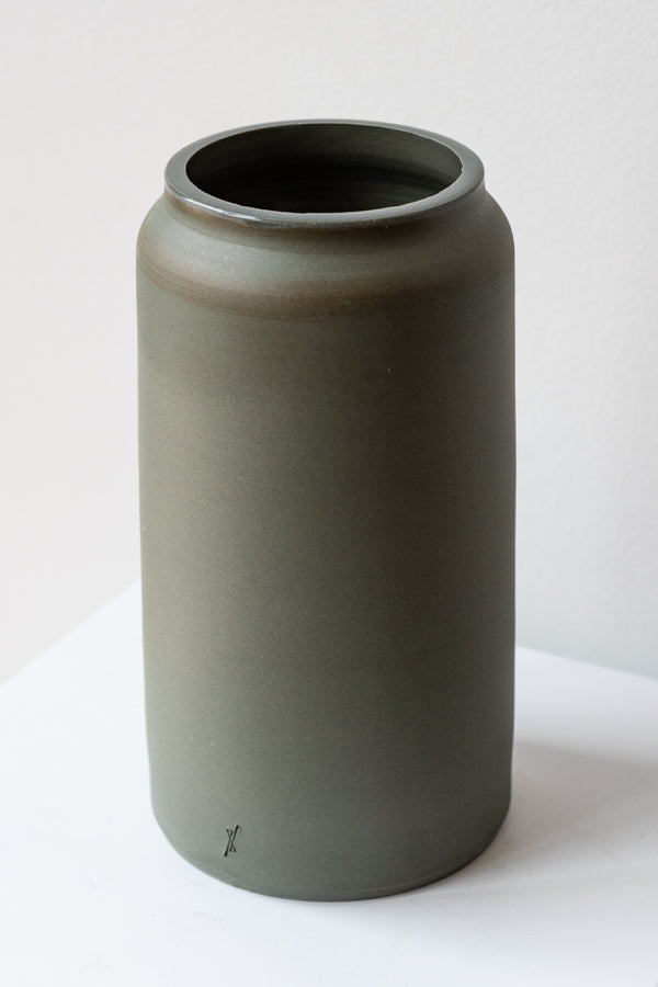 One medium green-grey stoneware vase sits on a white surface in a white room. It is round and tall, and it has a small logo imprinted at the base of the vase. It is photographed closer and at an angle.