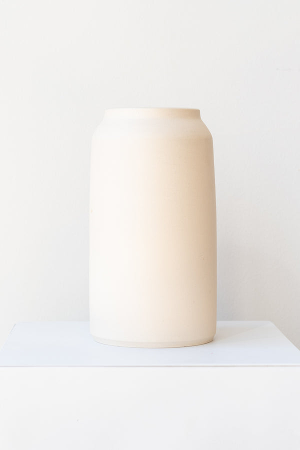 One cream colored bouquet vase sits on a white surface in a white room. The vase is tall and cylindrical, with a slight rim at the top. It is photographed straight on.