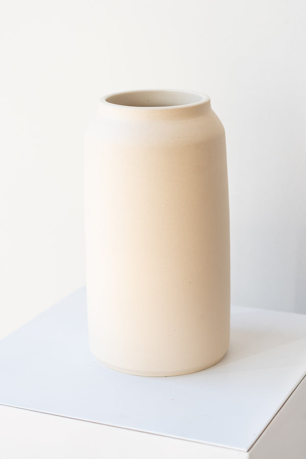 One cream colored bouquet vase sits on a white surface in a white room. The vase is tall and cylindrical, with a slight rim at the top. It is photographed at a slight angle to show the clay detail.