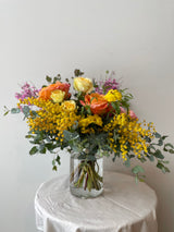 Midday floral arrangement by sprout home sits in a glass vase on a white table in a white room. THe arrangement is made up of yellow, pink, and light purple flowers with green foliage.