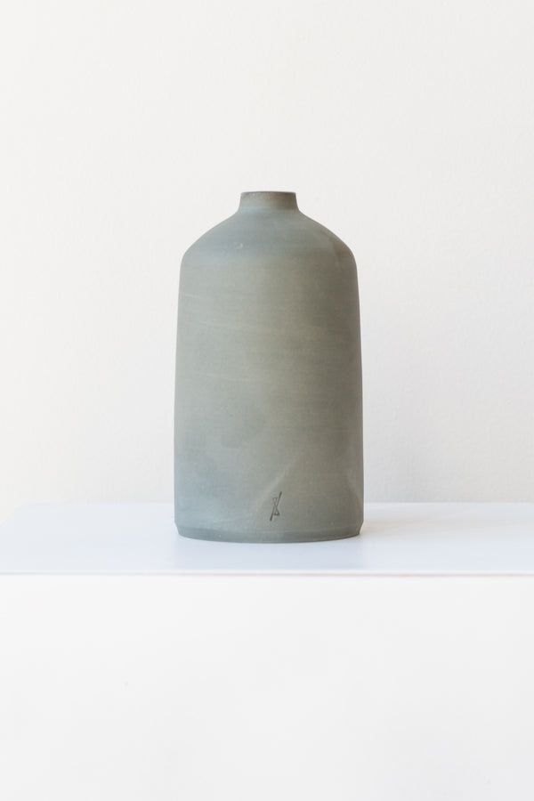 One grey stoneware bud vase sits on a white surface in a white room. It is short and cylindrical with a narrow opening at the top. It has a tiny logo imprinted in the bottom of the clay. It is photographed straight on.