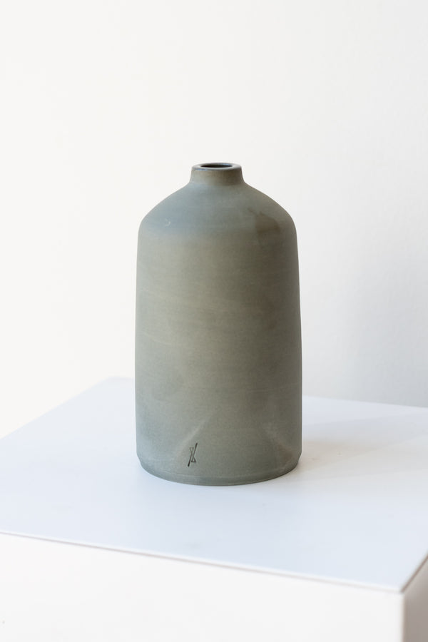 One grey stoneware bud vase sits on a white surface in a white room. It is short and cylindrical with a narrow opening at the top. It has a tiny logo imprinted in the bottom of the clay. It is photographed at a slight angle to show details in the clay.