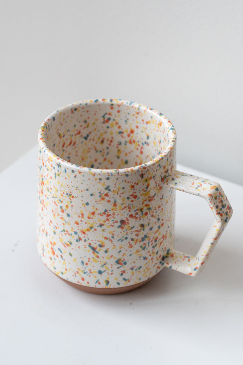 Color chips confetti mug by Miya Company Inc sits on a white surface in a white room