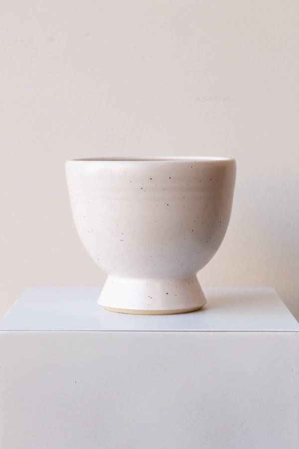 One glazed stoneware planter sits on a white surface in a white room. The planter is white with tiny black specks. The planter has a small angled base with a larger bowl shaped top. It is photographed straight on.