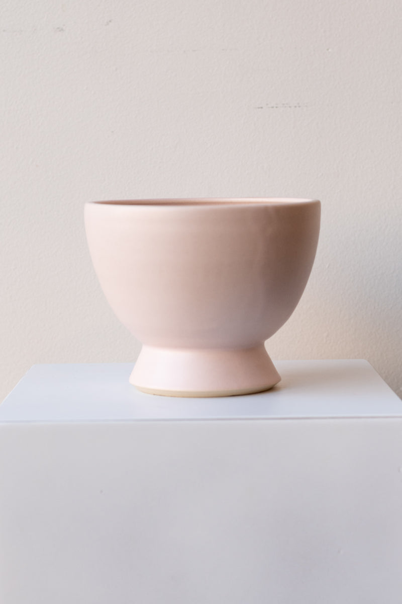 One glazed stoneware planter sits on a white surface in a white room. The planter is light pink. The planter has a small angled base with a larger bowl shaped top. It is photographed straight on.