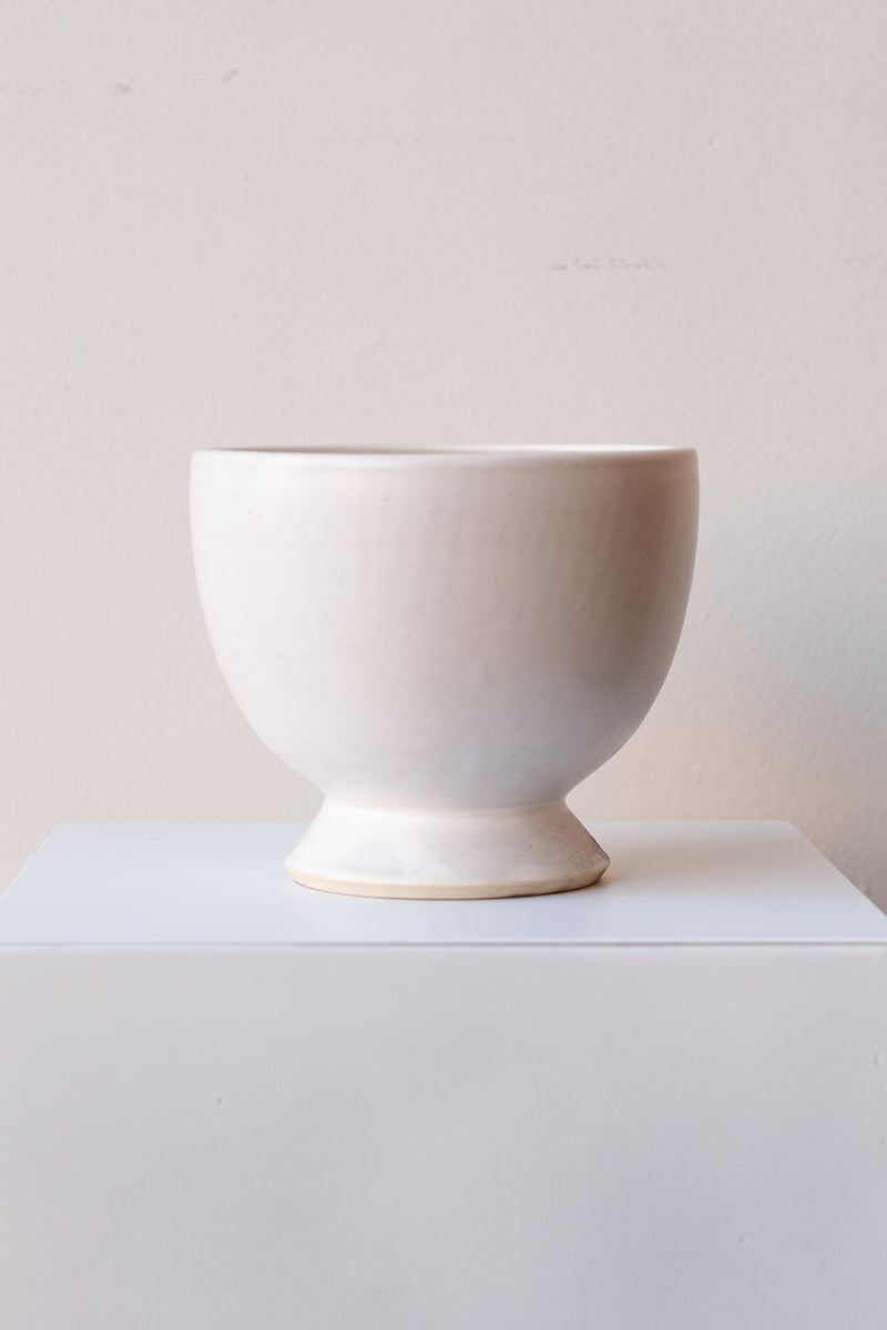 One glazed stoneware planter sits on a white surface in a white room. The planter is white. The planter has a small angled base with a larger bowl shaped top. It is photographed straight on.