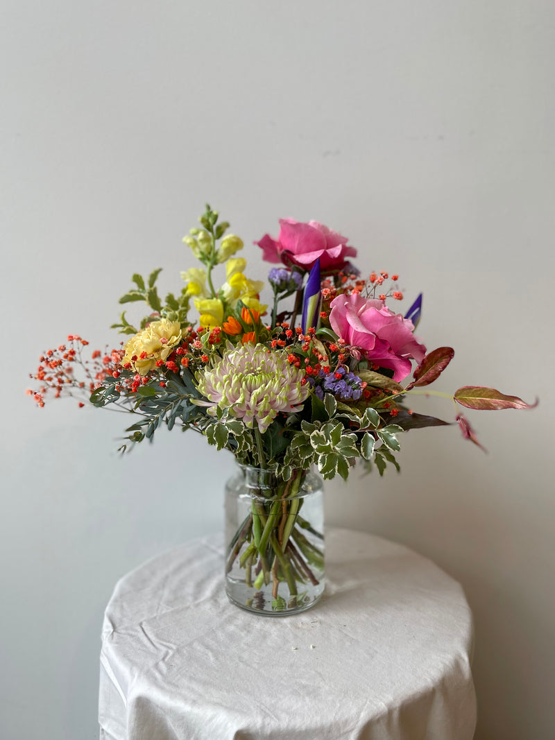 Midday floral arrangement by sprout home sits in a glass vase on a white table in a white room. The arrangement is made up of yellow, pink, red, and light purple flowers with green foliage.