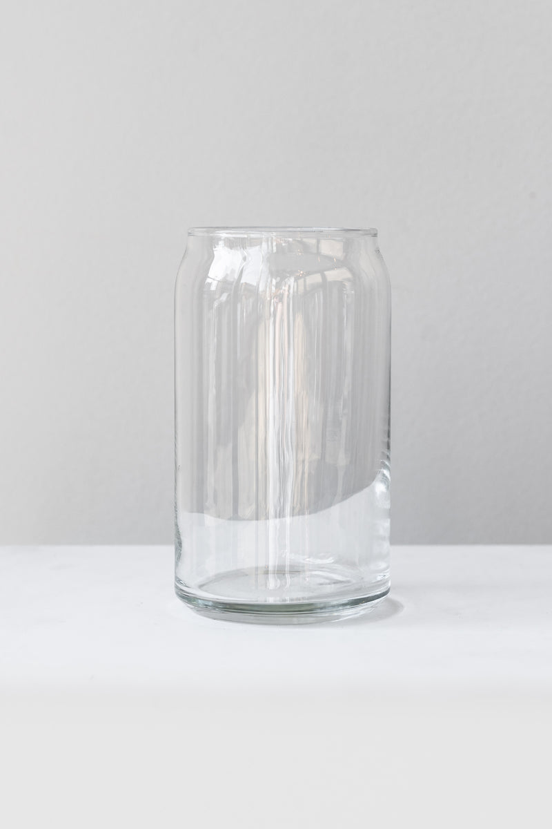 Clear glass jar sits on a white surface in a white room. The jar is shaped like a soda can. It is photographed straight on.