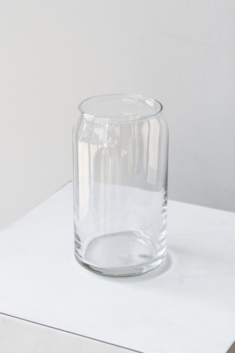 Clear glass jar sits on a white surface in a white room. The jar is shaped like a soda can. It is photographed closer and at an angle.