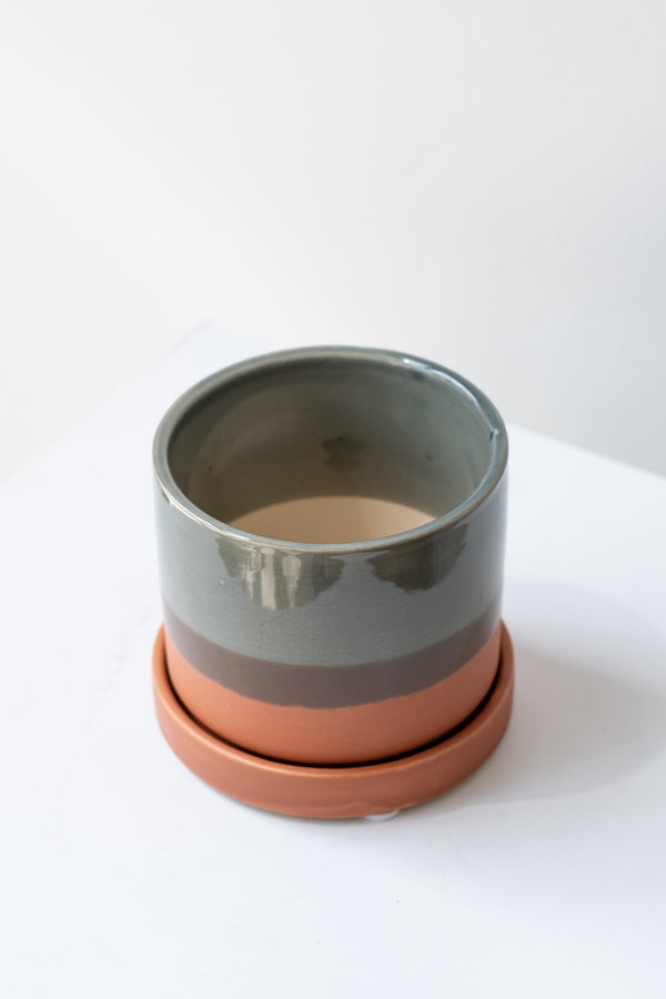Small Terracotta Minute Pot sits on a white surface in a white room