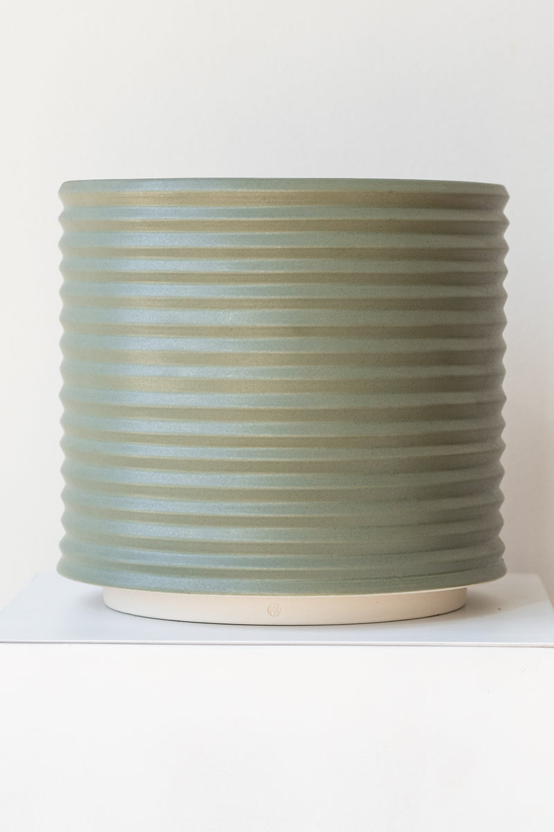 A large grey-green planter sits on a white surface in a white room. The planter is cylindrical and ribbed. It sits on an unglazed ceramic drainage tray. The planter is empty. It is photographed straight on.