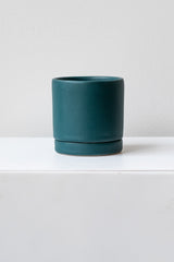 A small dark teal ceramic planter sits on a white surface in a white room. The planter has a matching drainage tray. The planter is empty. It is photographed straight on.