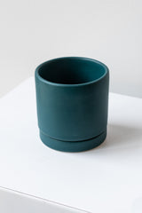 A small dark teal ceramic planter sits on a white surface in a white room. The planter has a matching drainage tray. The planter is empty. It is photographed closer and at an angle.