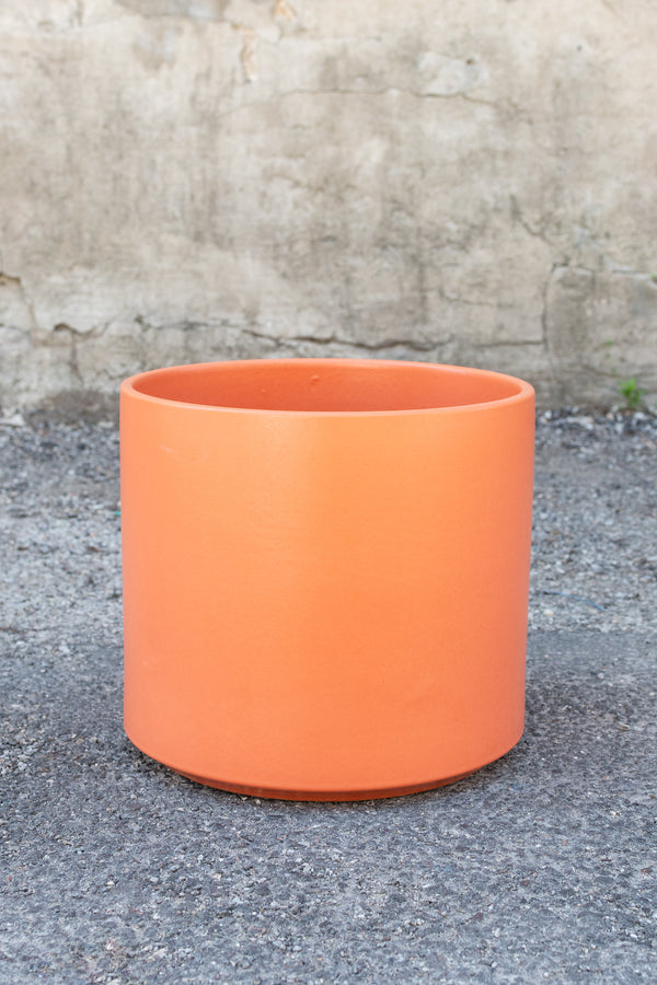 Rust solid cylinder planter by LBE designs sits in front of a concrete wall
