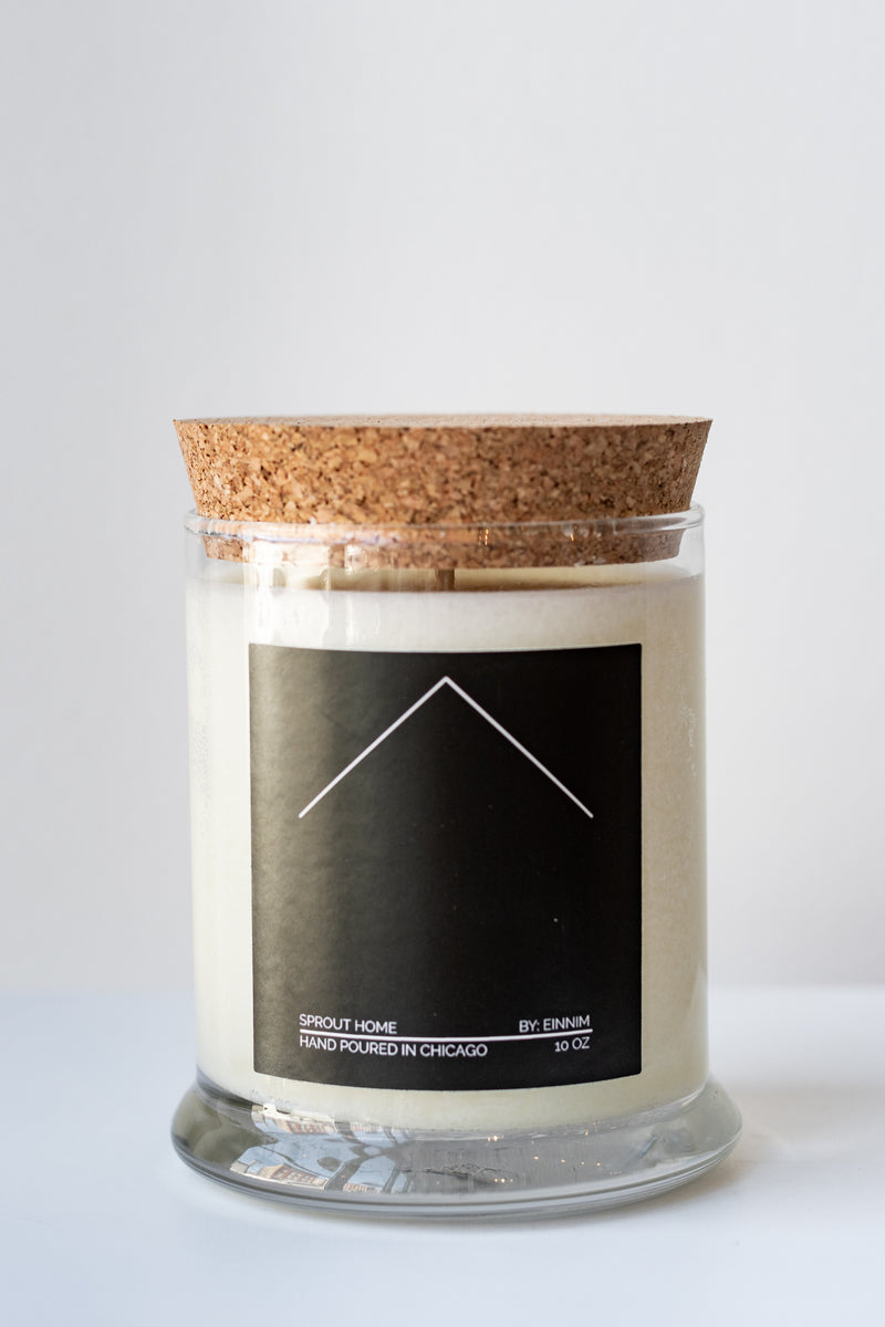 "A white candle in a glass jar sits on a white surface in a white room. The candle has a cork lid and a black label with white text. The text reads: ""sprout home, by: einnim, hand poured in Chicago, 10 oz"""