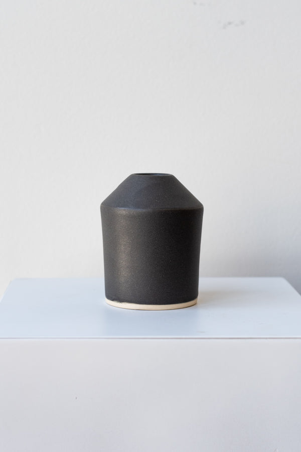 One small ceramic vase sits on a white surface in a white room. The vase is cylindrical and tapers off at the top to a narrow opening. The vase is black with a small ring of unglazed clay at the bottom. It is photographed straight on.