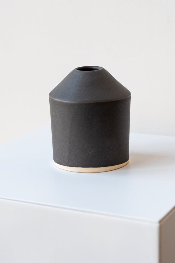 One small ceramic vase sits on a white surface in a white room. The vase is cylindrical and tapers off at the top to a narrow opening. The vase is black with a small ring of unglazed clay at the bottom. It is photographed closer and at an angle.