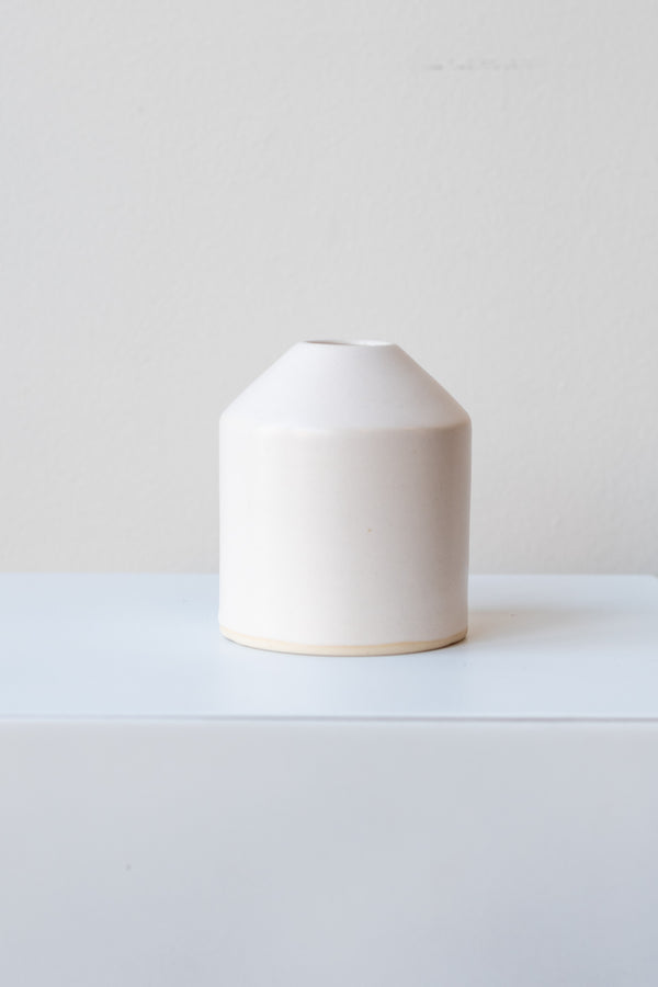 One small ceramic vase sits on a white surface in a white room. The vase is cylindrical and tapers off at the top to a narrow opening. The vase is white with a small ring of unglazed clay at the bottom. It is photographed straight on.