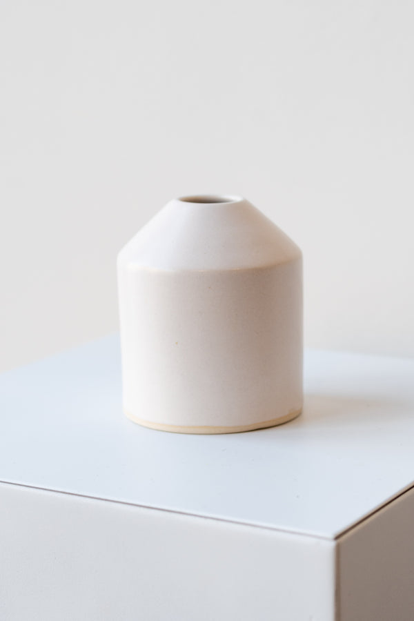 One small ceramic vase sits on a white surface in a white room. The vase is cylindrical and tapers off at the top to a narrow opening. The vase is white with a small ring of unglazed clay at the bottom. It is photographed closer and at an angle.