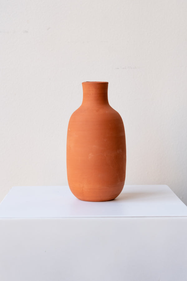 One terra cotta bud vase sits on a white surface in a white room. The vase is round and shaped like a bottle. The vase is empty. It is photographed straight on.