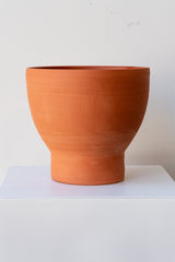 One terra cotta vase sits on a white surface in a white room. The vase is cylindrical at the bottom with a wider bowl shaped top. The vase is empty. It is photographed straight on.